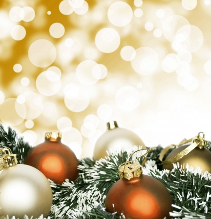 twinkling: An arrangement of golden Christmas baubles against a festive bokeh of twinkling gold lights with copyspace