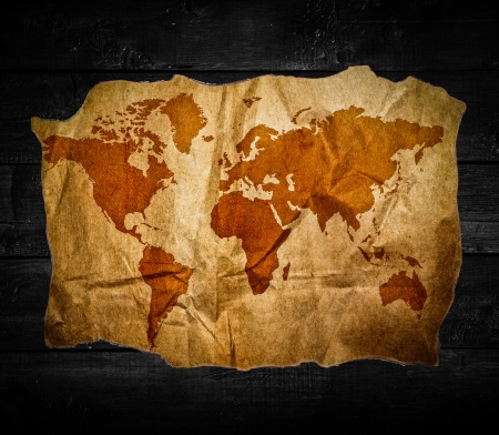 Antique world map in black wooden background photo