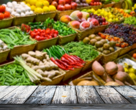 fruit market: Background with empty wooden table and blured fruits and vegetables Stock Photo