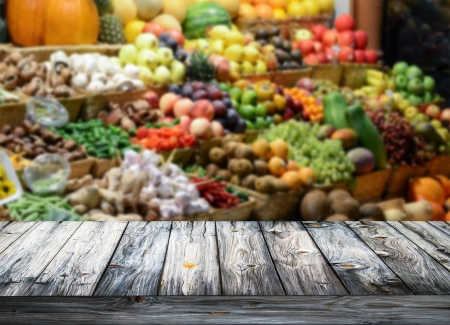 Background with empty wooden table and blured fruits and vegetables photo