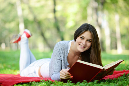Beautiful smiling woman reading book in park photo