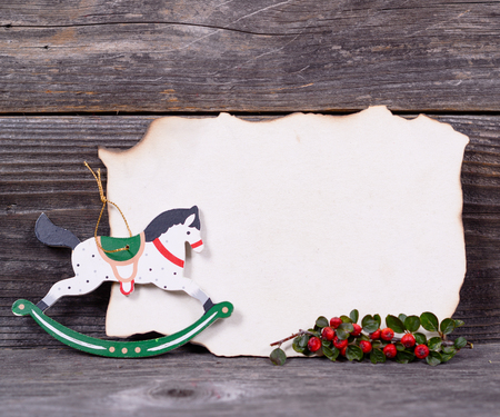 Christmas background with empty paper and wooden horse decoration and berries photo