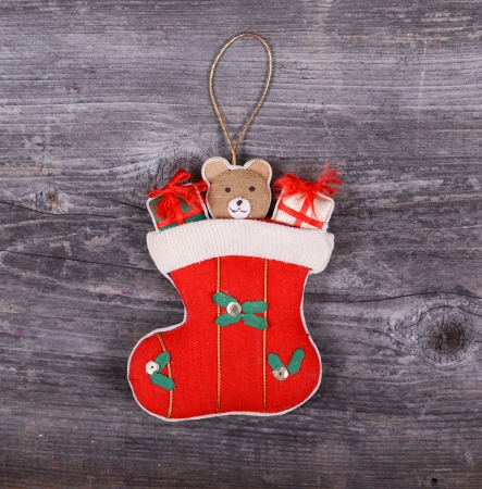 Christmas decorative ornament - Gifts in sock horses on wooden background photo