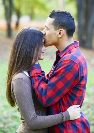 Close up of boy kissing girlfriend on forehead outdoor photo