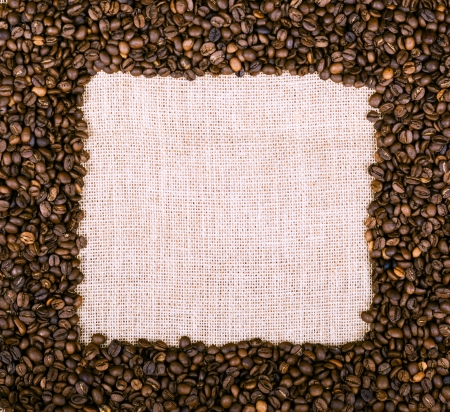 Coffee beans frame over burlap textile photo