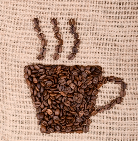 Coffee cup image made up of coffee beans on canvas background photo