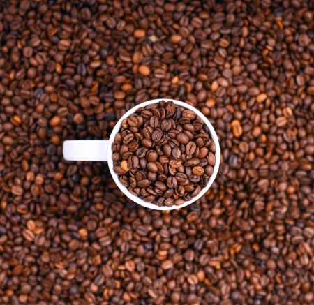 Cup of coffee filled with coffee beans photo