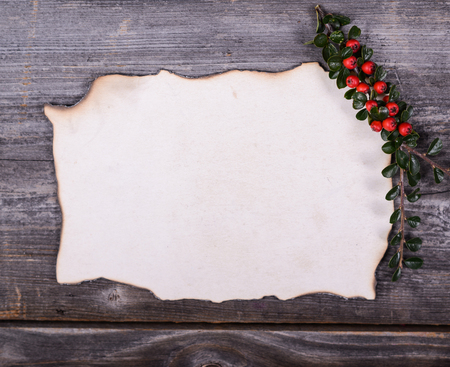Empty paper note for Santa Claus with red berries on wooden background photo