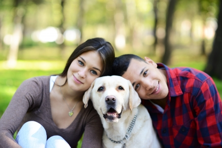 Happy couple with puppy dog at park photo