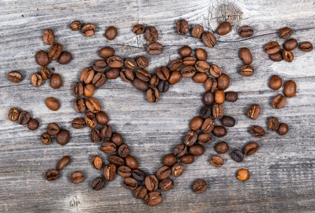Heart shape made from coffee beans on wooden background photo