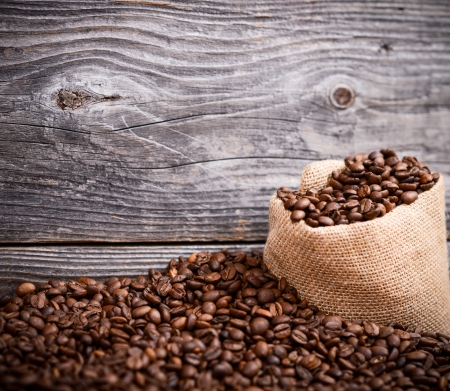 Sack of coffee grains against grunge wooden wall photo