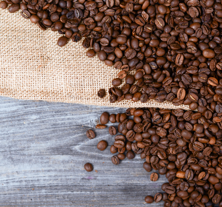 Sack of coffee grains on wooden background photo