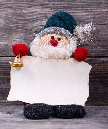 Santa Claus toy holding empty paper against wooden background photo