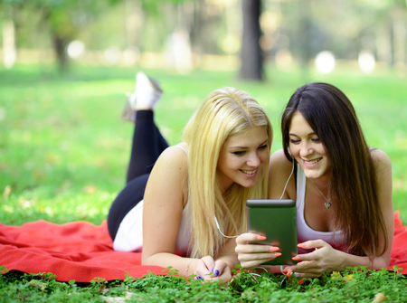 Teenage girls having fun online on digital tavblet outdoors in park photo