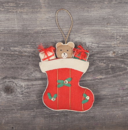 Vintage Christmas decorative ornament - Gifts in sock horses on wooden background photo