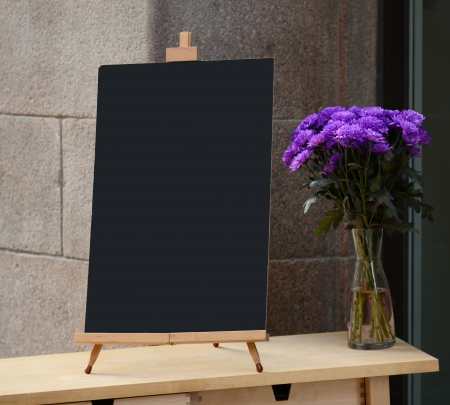 Wooden board for restaurant menu with empty space to add text standing at restaurant entrance with flower pot photo