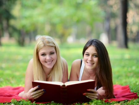 Two girls reading book in park photo