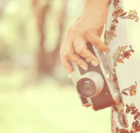 Woman hand holding retro camera close-up photo