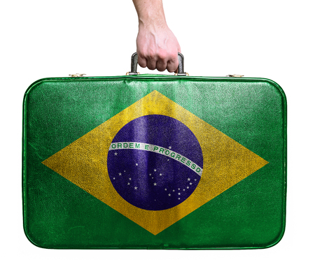 Tourist hand holding vintage leather travel bag with flag of Brazil photo