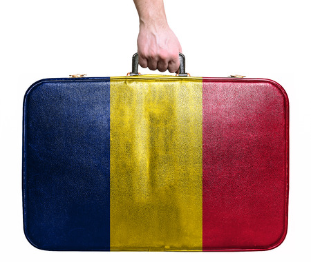 Tourist hand holding vintage leather travel bag with flag of Chad Stock Photo