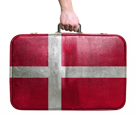 Tourist hand holding vintage leather travel bag with flag of Denmark photo