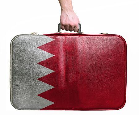 bahrain money: Tourist hand holding vintage leather travel bag with flag of Bahrain Stock Photo