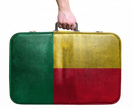 benin: Tourist hand holding vintage leather travel bag with flag of Benin