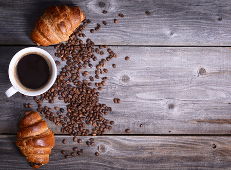 Coffee and fresh croissant on wooden