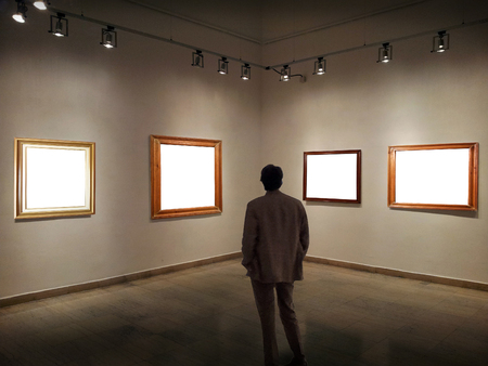 Man in gallery room looking at empty picture frames