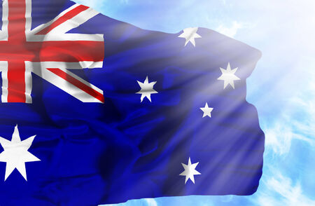 flag australia: Australia waving flag against blue sky with sunrays