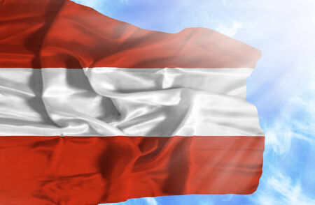 Austria waving flag against blue sky with sunrays photo