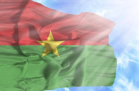 burkina faso: Burkina Faso waving flag against blue sky with sunrays