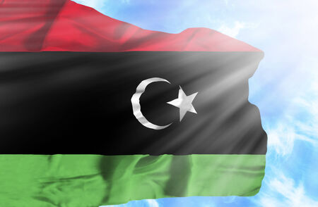 Libya waving flag against blue sky with sunrays photo