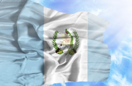 Guatemala waving flag against blue sky with sunrays photo
