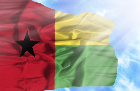 bissau: Guinea Bissau waving flag against blue sky with sunrays Stock Photo