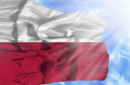 Poland waving flag against blue sky with sunrays photo