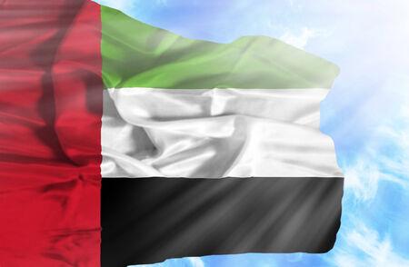 arab flags: United Arab Emirates waving flag against blue sky with sunrays Stock Photo
