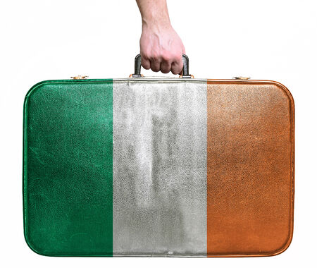 Tourist hand holding vintage leather travel bag with flag of Ireland photo