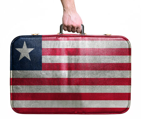liberia: Tourist hand holding vintage leather travel bag with flag of Liberia