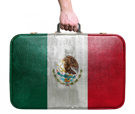Tourist hand holding vintage leather travel bag with flag of Mexico photo