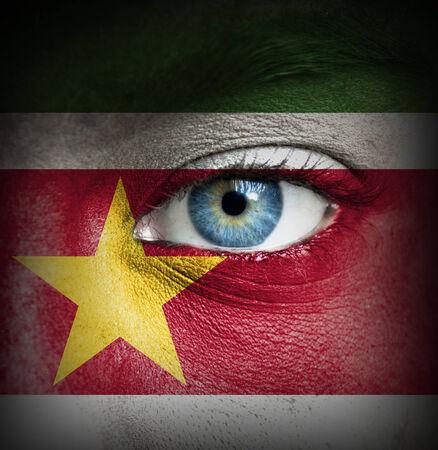 suriname: Menselijk gezicht beschilderd met vlag van Suriname