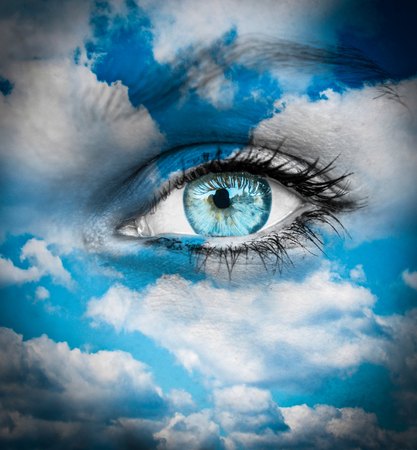 Beautiful blue eye against blue clouds - Spiritual concept photo