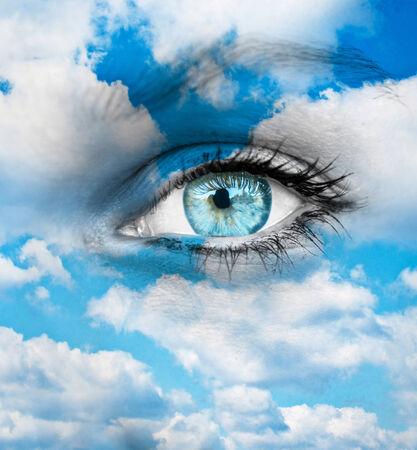 dilate: Beautiful blue eye against blue clouds - Spiritual concept Stock Photo
