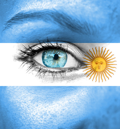 Woman face painted with flag of Argentina