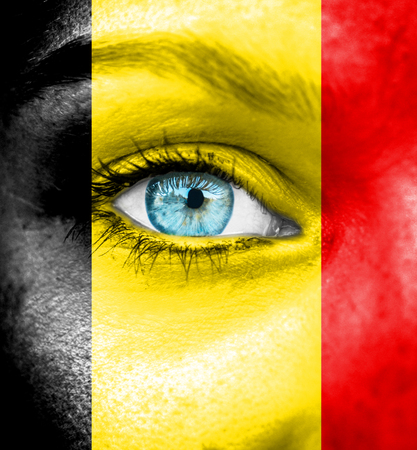 Vrouw gezicht beschilderd met de vlag van België Stockfoto