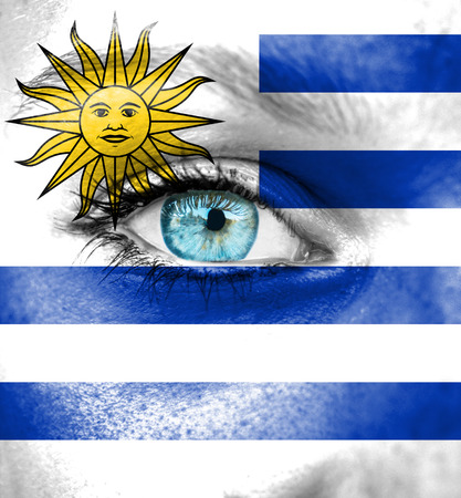 Woman face painted with flag of Uruguay photo