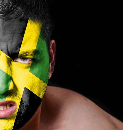 jamaican adult: Portrait of angry man with painted flag of Jamaica Stock Photo