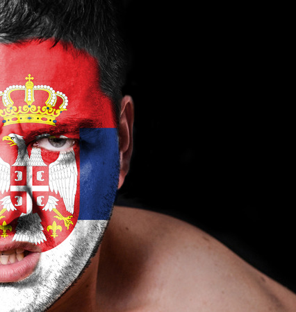 Portrait of angry man with painted flag of Serbia photo