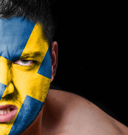 Portrait of angry man with painted flag of Sweden photo