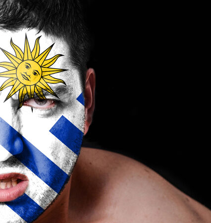 Portrait of angry man with painted flag of Uruguay photo
